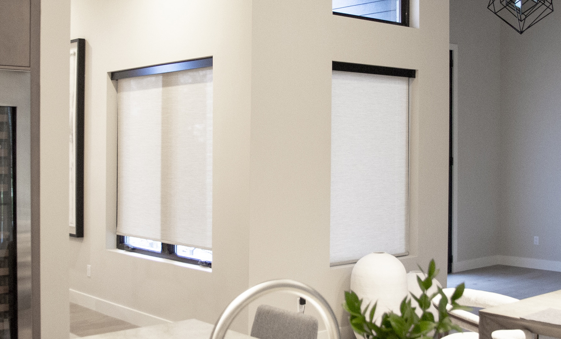 kitchen with two windows that are covered by white interior roller shades
