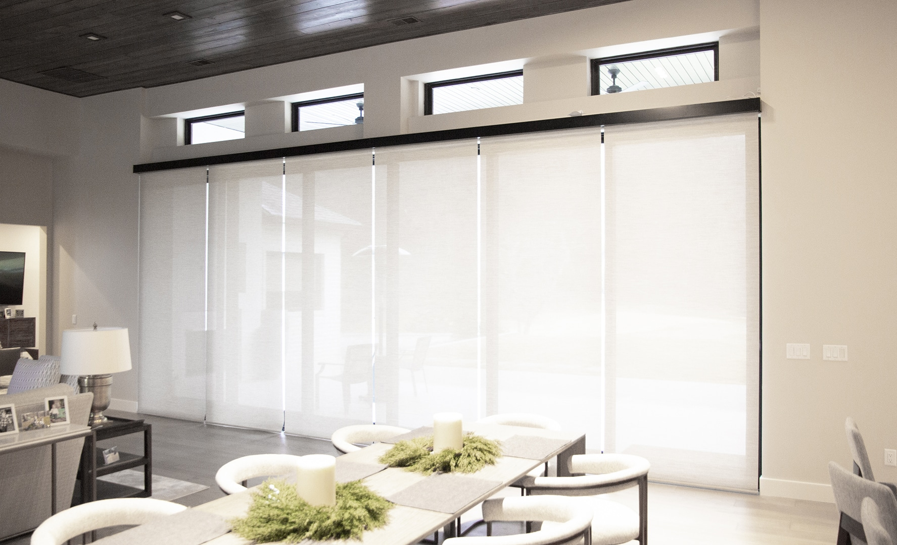 living room with a large window covered by off-white coupled interior roller shades