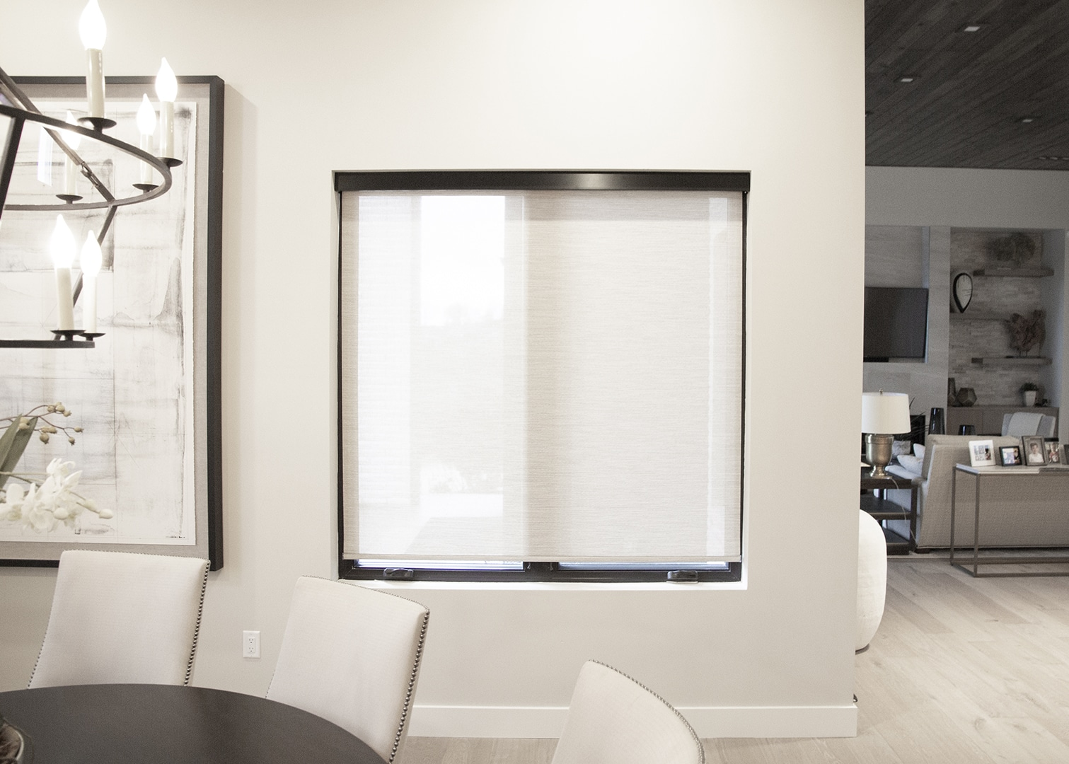 white modern dining room with a fully closed interior roller shades